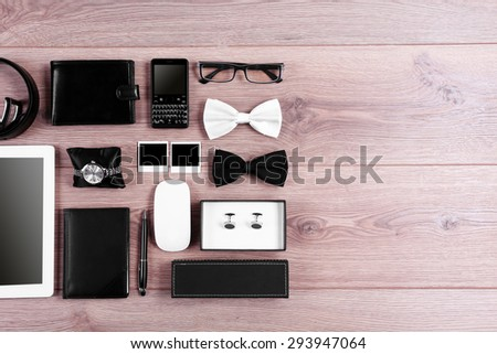 Set of black and white accessories on wooden table, top view - stock photo