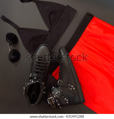 Set of black leather shoes with spikes with sunglasses, black bodice and orange skirt, on black background