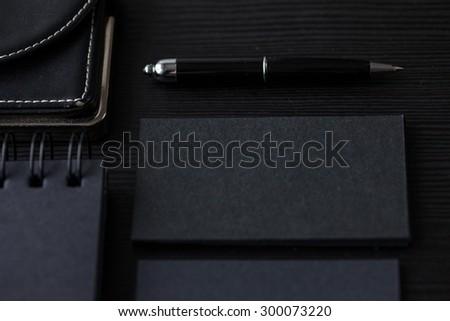 Set of black mockups on dark background,  female hand holding a business card - stock photo