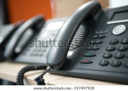 Set of black telephones on a desk, receiver close-up. - stock photo