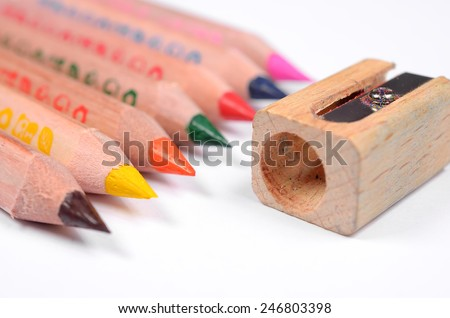 Set of bright colored pencils and knife-sharpener on a white background - stock photo