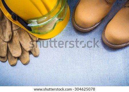 Set of brown safety waterproof shoes leather gloves hard hat and working glasses on scratched metallic background construction concept. - stock photo