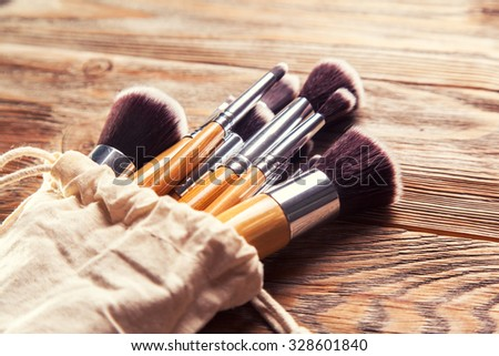 set of brushes for makeup scattered chaotically on wooden background - stock photo