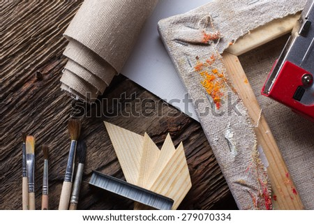 Set of brushes for painting, canvas, stapler, staples, subframe and blank white paper on old grunge natural wooden shabby desk background in painter studio. Top view. - stock photo