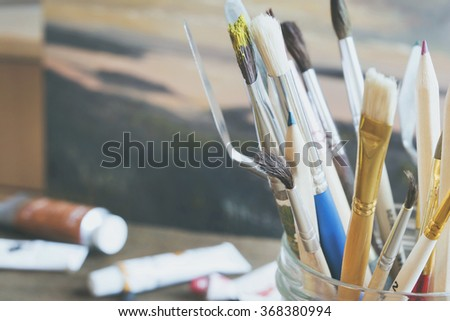 set of brushes for painting pencils spatula in the bank against the backdrop of paintings and oil paints on the wooden table