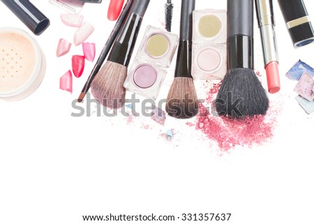 set of  brushes, lipsticks and  eye  shadows with crumbles  isolated on white background