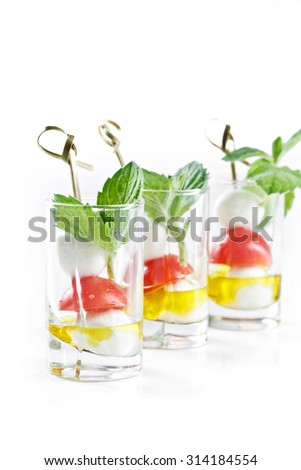 set of canapes in glass with mozarella, tomato and olive oil greece salad - stock photo