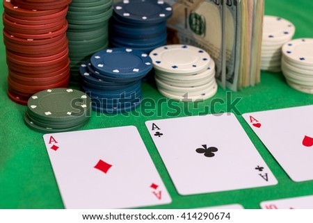 Set of casino chips, money and poker cards on green cloth