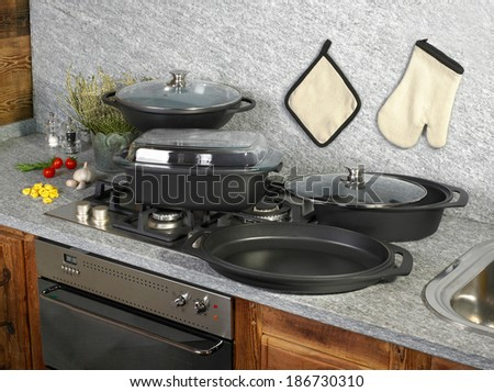 set of cast-iron pots on a kitchen working surface. - stock photo