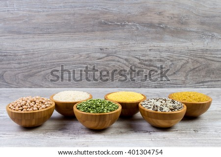 Set of cereals, peas, rice, millet, chickpeas sprinkled in bamboo bowls - stock photo