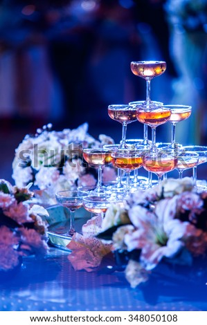 Set of champagne and wedding bouquet in outdoor wedding party at night in blue light image - stock photo