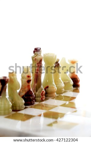 Set of chess pieces made from Onyx on board against white background - stock photo