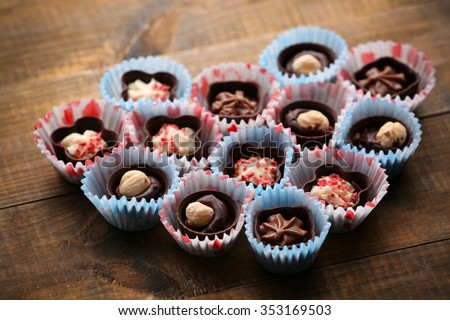 Set of chocolate candies forming heart on a wooden background