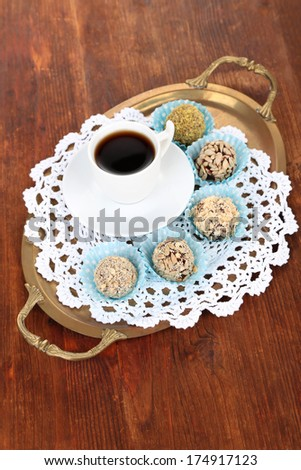 Set of chocolate candies, on tray, on wooden background