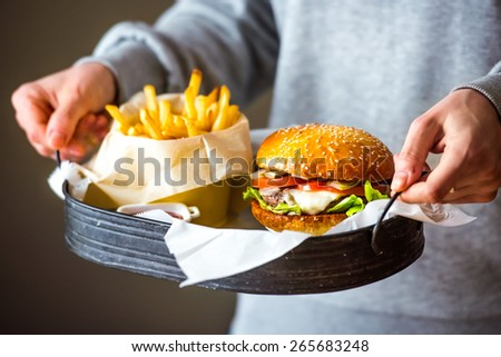 Set of classic american cheese burger and french fries in hands - stock photo