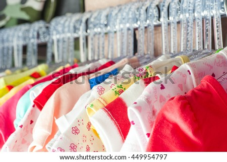 Set of clothes for kids on hangers. Shopping. Toned image.