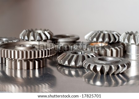 Set of cogwheels on a polished to a shine steel surface - stock photo
