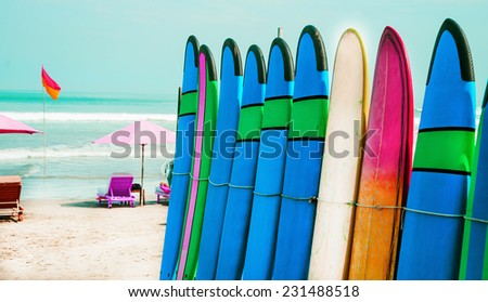 Set of color surf boards in a stack by ocean - stock photo