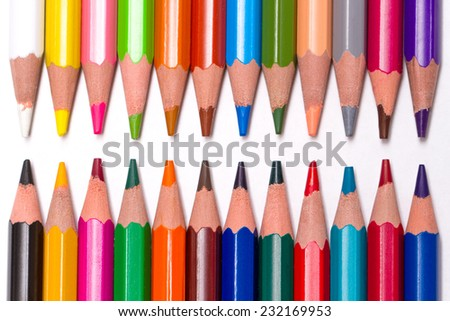set of colored pencils lie on a white table