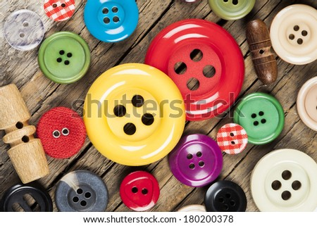 Set of colored sewing buttons on wooden background - stock photo