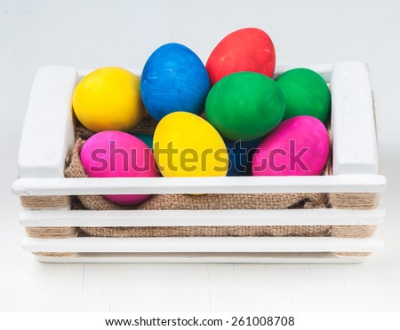 Set of colorful Easter eggs in a white wooden box.