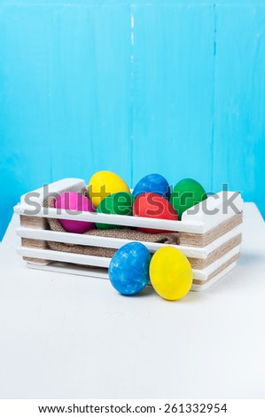 Set of colorful Easter eggs in a white wooden box on blue backgrounds.