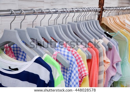 Set of colorful female clothing on hanging in store - stock photo