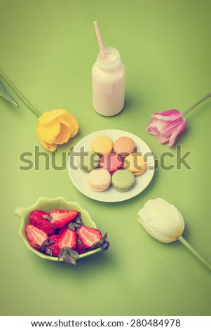 Set of colorful macaroons on plate, tulip flowers, strawberry, milk cocktail in bottle with straw on green background. Filtered look - stock photo