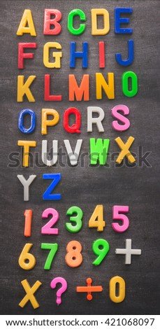set of colorful plastic alphabet on chalkboard background