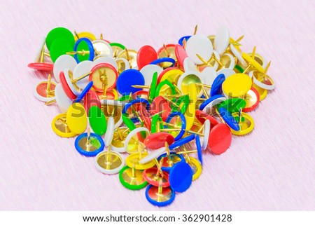 Set of colorful thumbtacks arranged in heart shape. Close-up on pink background. - stock photo