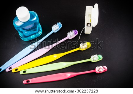 Set of colorful toothbrush with mountwash and dental floss on wooden board - stock photo
