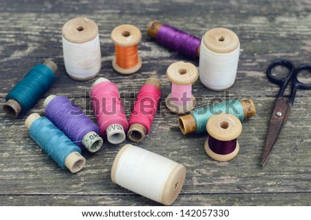 Set of colorful vintage thread spools on rusted wooden table - stock photo