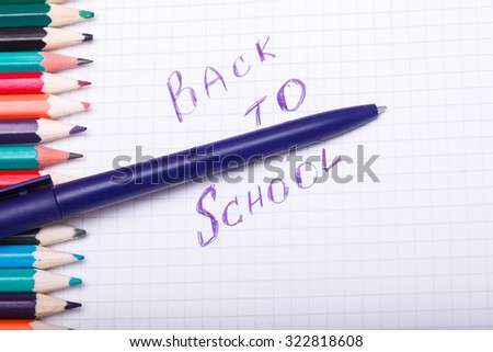 Set of colorful wooden pencils yellow green red pink orange blue and brown lying in row on table with white paper sheet with back to school text, horizontal picture - stock photo