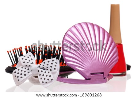 Set of cosmetics - nail polish, small mirror and comb on white background - stock photo