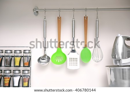 Set of cutlery hanging on wall in the kitchen - stock photo