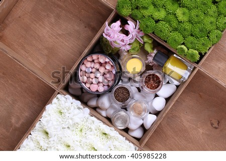 set of decorative cosmetic powder, concealer, eye shadow brush, blush, foundation, lipstick, nail polish, face and body cream, perfume and flowers in wood cell.