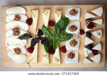 Set of delicious appetizing cheese on wooden board cuisine ingredient food gourmet product decorated by walnut green leaf basil strawberry grape on wooden board background closeup top view, horizontal - stock photo