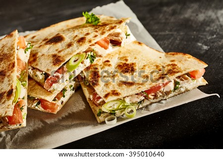 Set of delicious cooked wheat tortilla quesadillas with onion, tomato and herbs in wax paper on dark background - stock photo