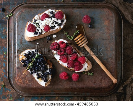 Set of dessert sandwiches with fresh berries blueberry and raspberry, cream cheese, thyme and honey, served with honey dipper over old dark iron textured background. Top view