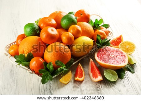 Set of different citrus fruit on light wooden background - stock photo