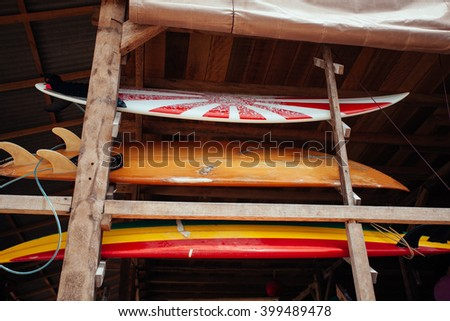 Set of different color surf boards in a stack by ocean.BALI. Surf boards on sandy Balangan beach. On Balangan beach.  surf is available all year around for beginner and advanced. - stock photo