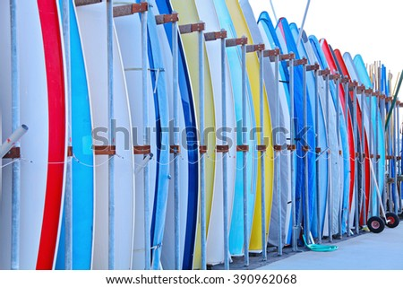 Set of different color surf boards in a stack by ocean in California on the beach