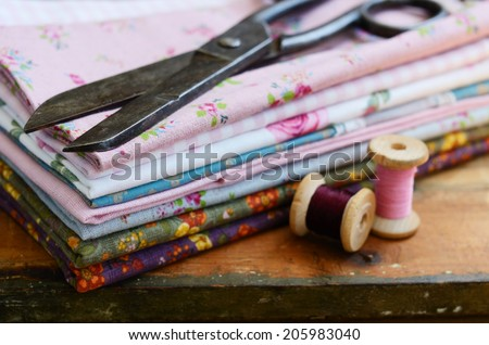 Set of different fabrics, wooden thread spools and tailor scissors on wooden background with selective focus on scissors - stock photo