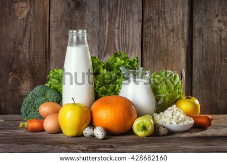 Set of different foods on the old wooden background, vegetables, fruit, eggs, dairy products, the concept of a balanced diet, vegetarian food - stock photo