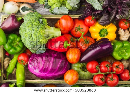 Set of different fresh raw colorful vegetables in the wooden tray, light background
