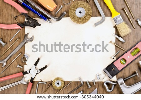 Set of different old Tools and paper on wooden background - stock photo