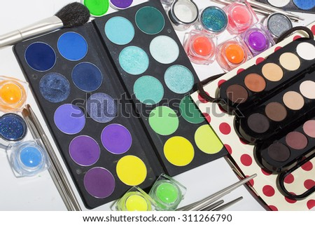 Set of different professional eyeshadow palette red orange green violet pink yellow purple black beige brown colors foundation powder and make-up brushes on white background, horizontal picture - stock photo