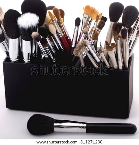 Set of different professional soft make-up brushes for eyeshadow powder and facial foundation for visagistes black and brown colors in plastic box on white background, square picture - stock photo