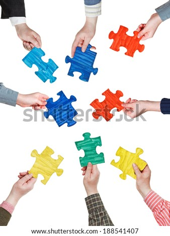 set of different puzzle pieces in people hands in circle isolated on white background