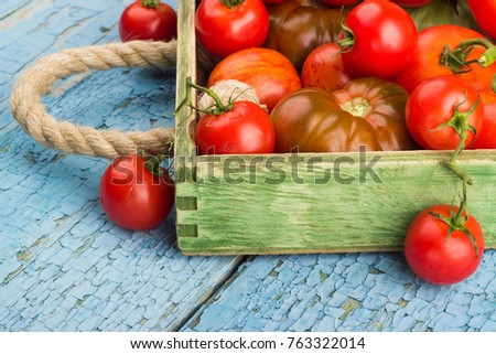 Set of different sorts of ripe tomatoes in the wooden tray, soft focus background